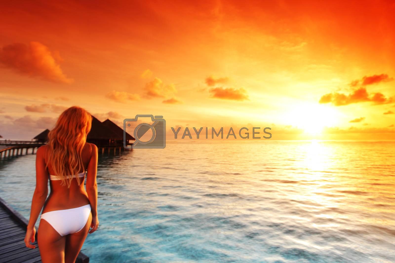 Happy young woman at beautiful water villa at Maldives island at sunset. Travel vacation tourist resort
