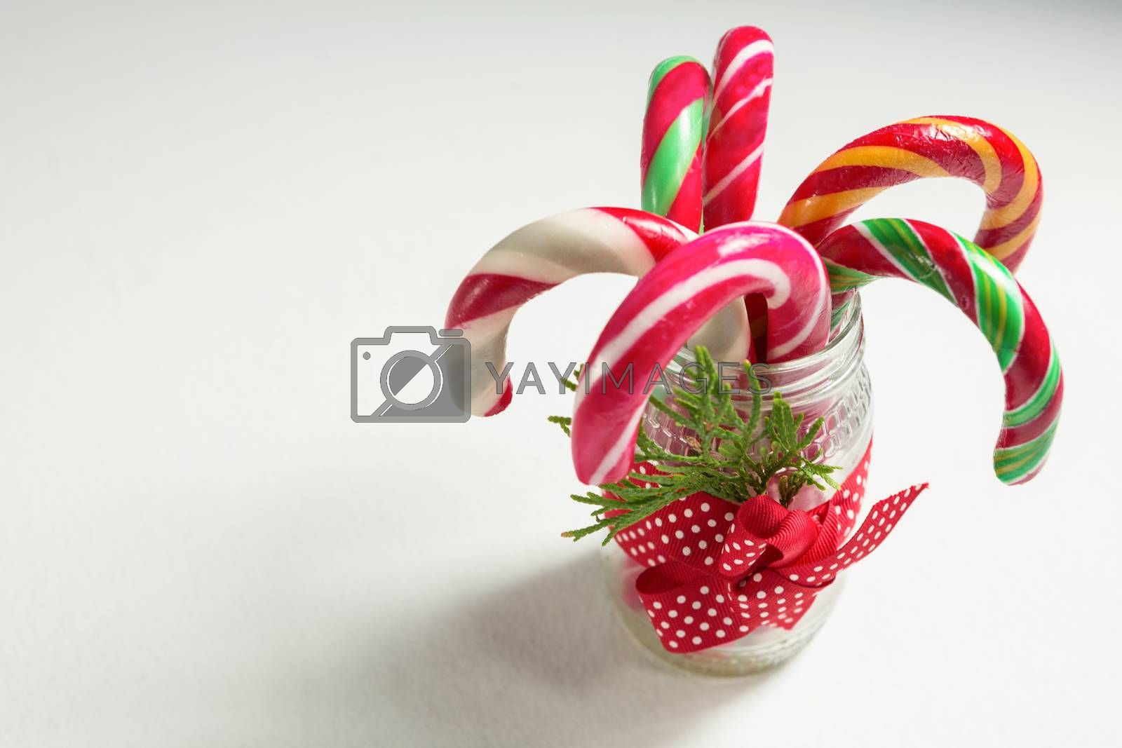 Close up of colorful candy canes in glass jar by Wavebreakmedia