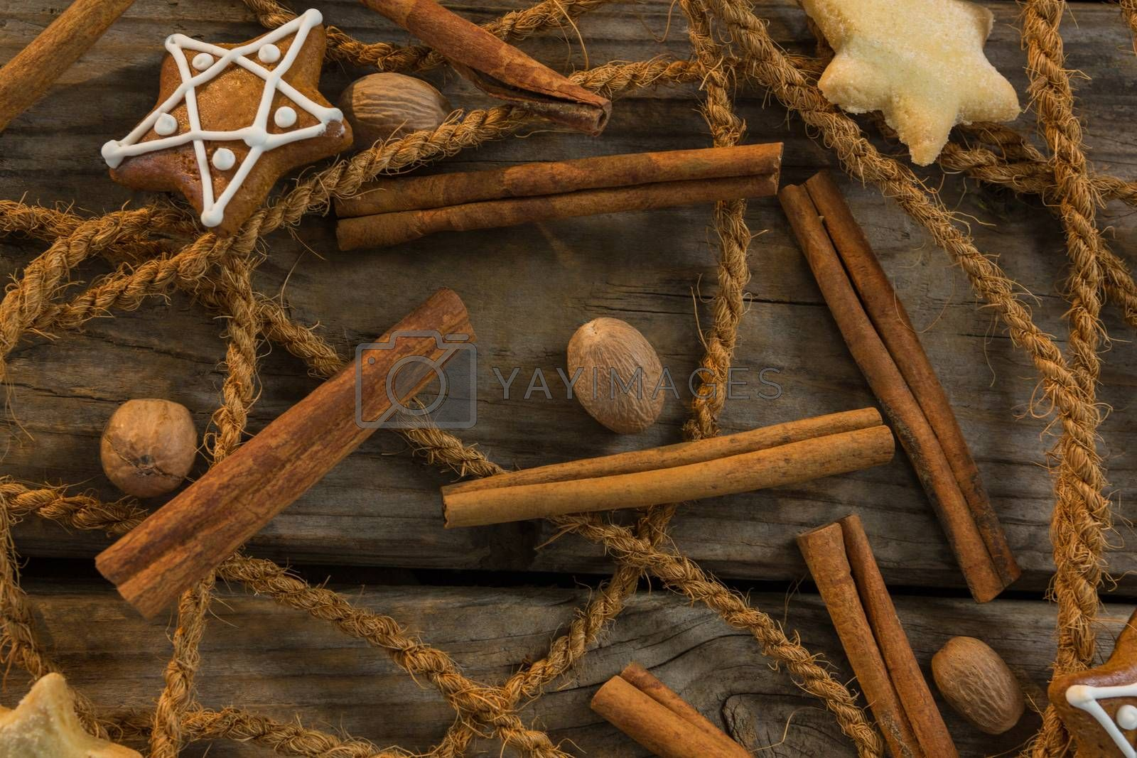 Overhead view of rope with star shape cookies and cinnamon sticks by walnuts by Wavebreakmedia