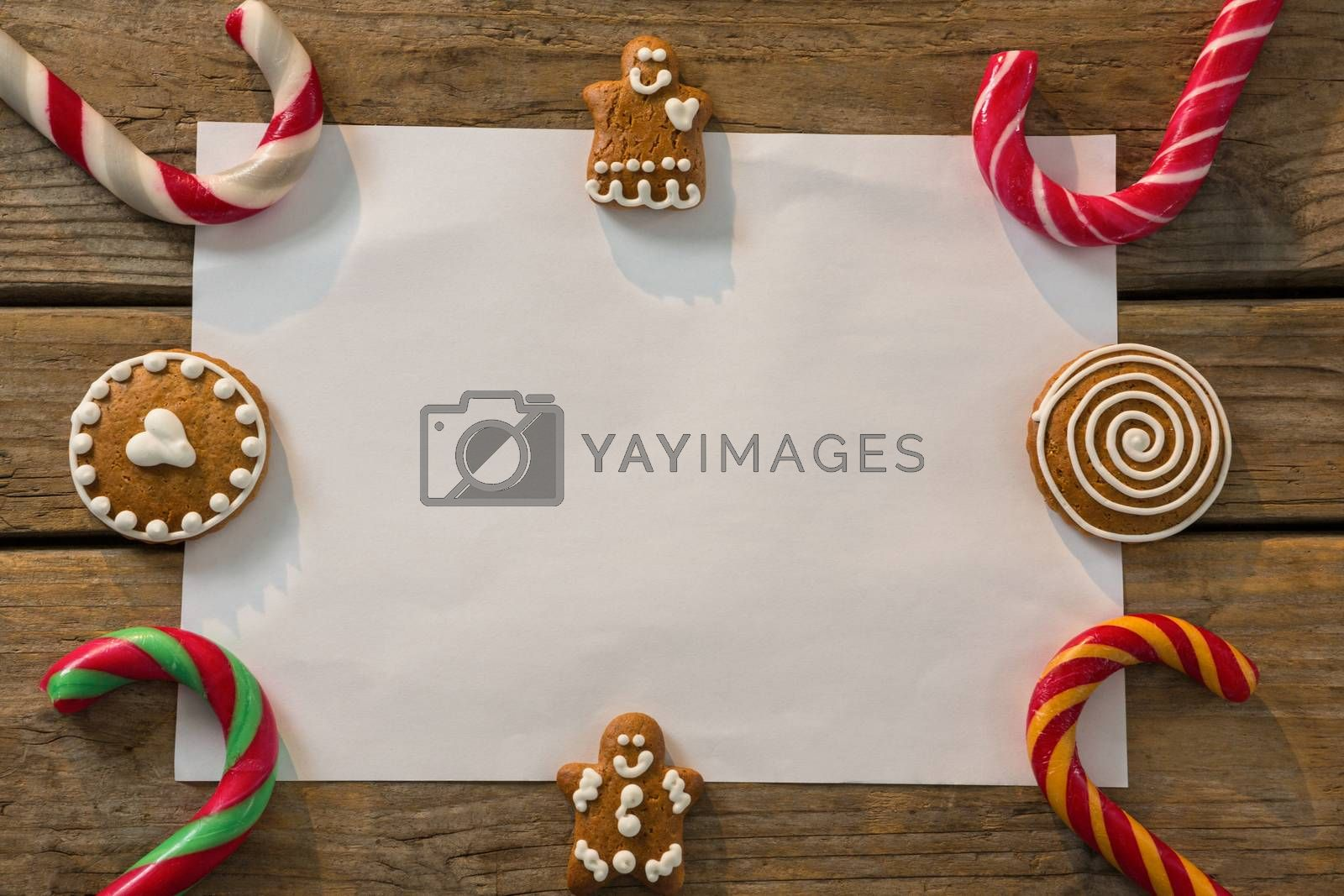 Overhead view of candy canes with gingerbread cookies and paper arranged on table by Wavebreakmedia