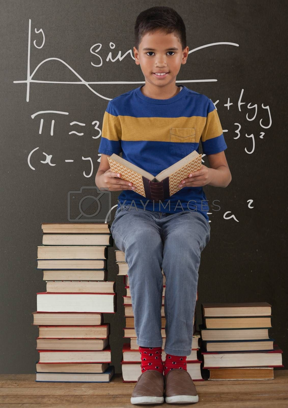 Happy student boy on a table reading against grey blackboard with education and school graphics by Wavebreakmedia