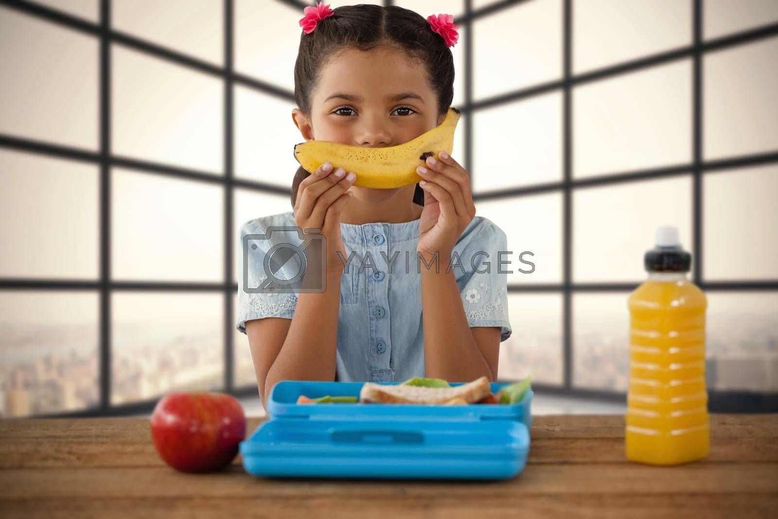 Composite image of girl holding banana at table by Wavebreakmedia