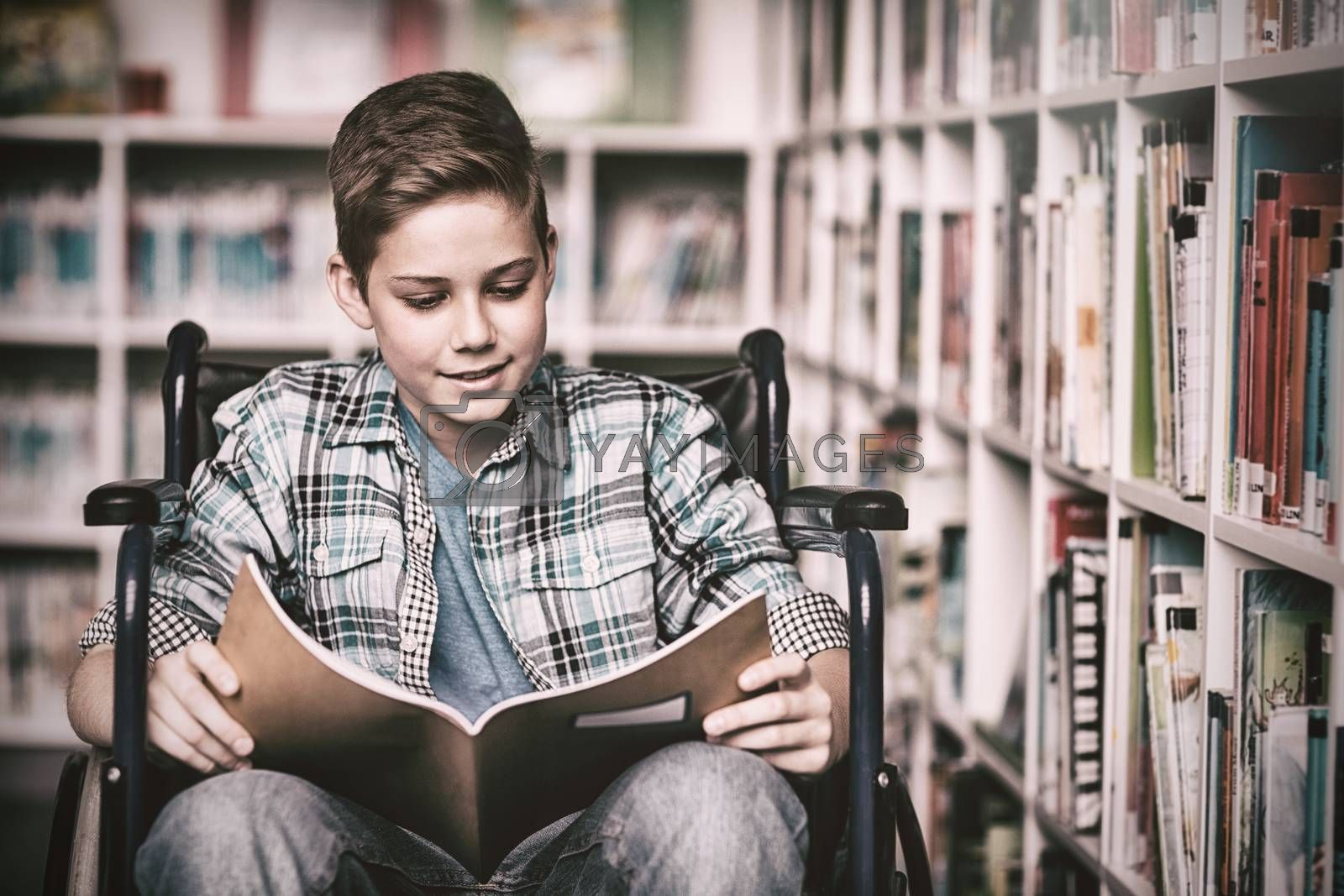 Disabled schoolboy reading book in library by Wavebreakmedia