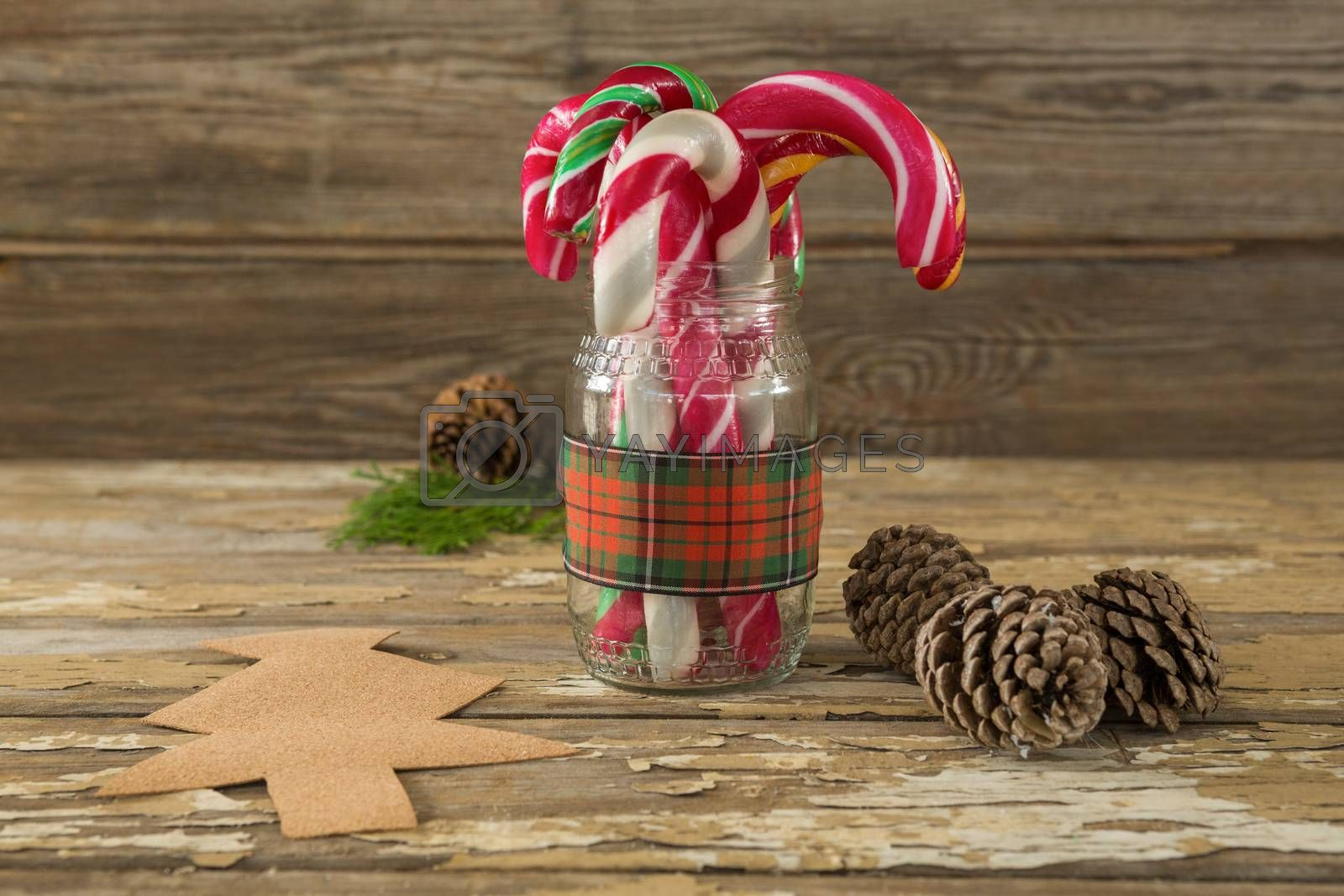 Pine cones and candy cane in jar against wooden plank by Wavebreakmedia