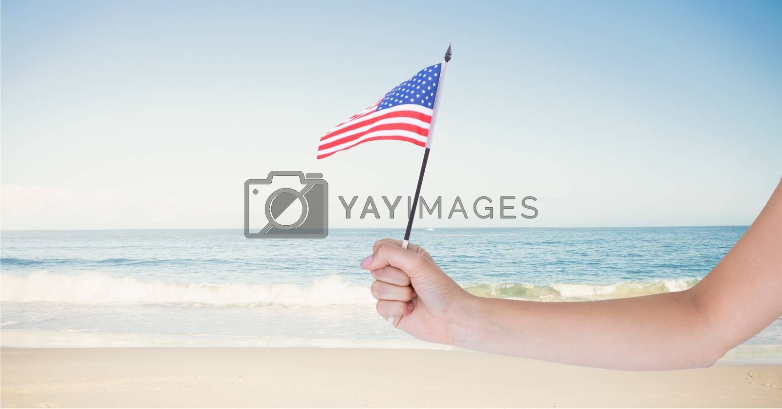 Person holding a USA flag in the beach by Wavebreakmedia