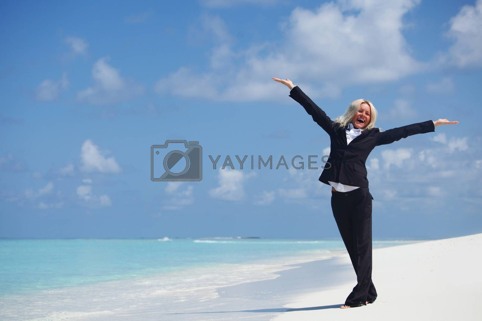 Happy business woman in formal suit with arms raised on the desolate ocean coast