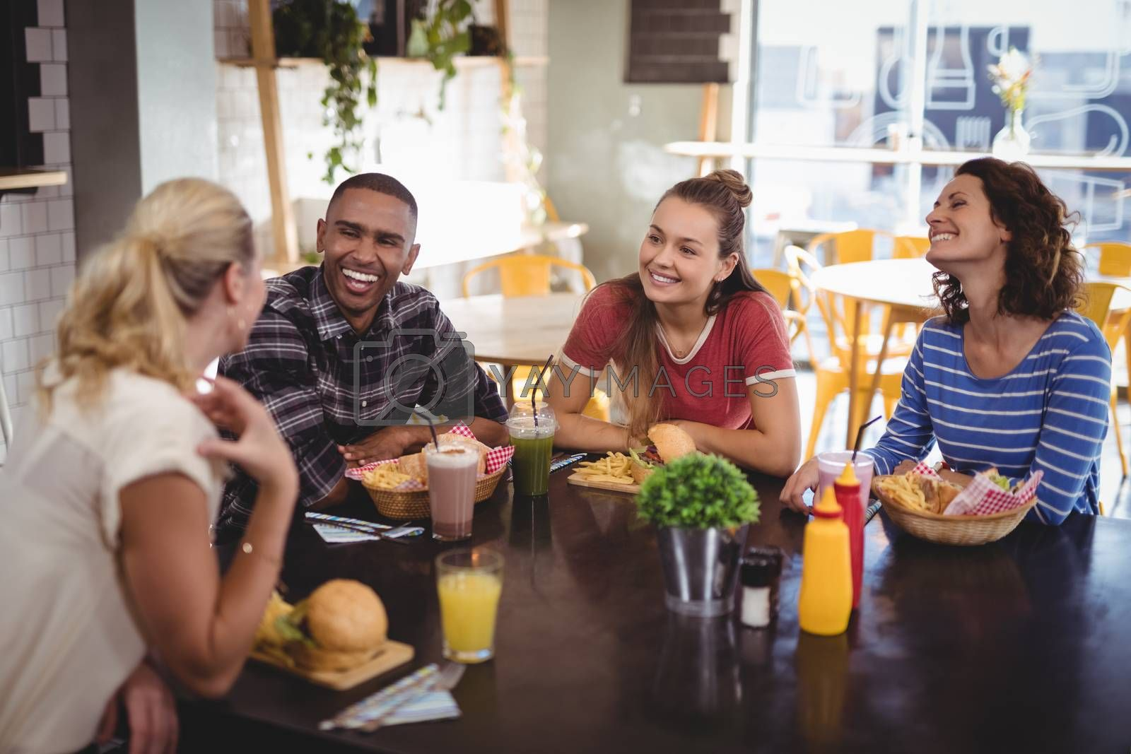 Young friends talking while sitting at table with food and drink at coffee shop