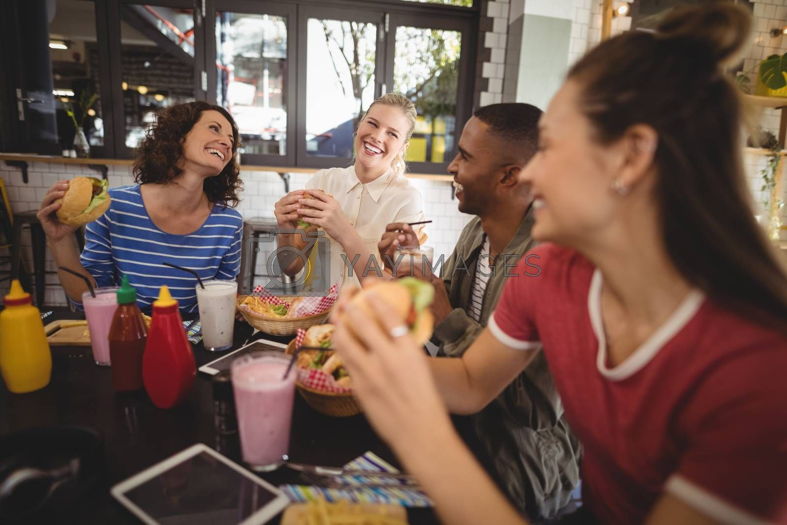 Cheerful young friends sitting with food and drink at table in coffee shop