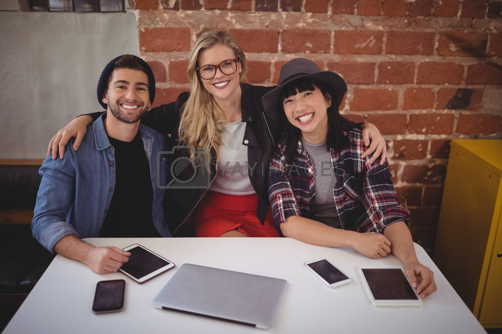 Portrait of smiling creative team sitting with technologies at table against brick wall in coffee shop