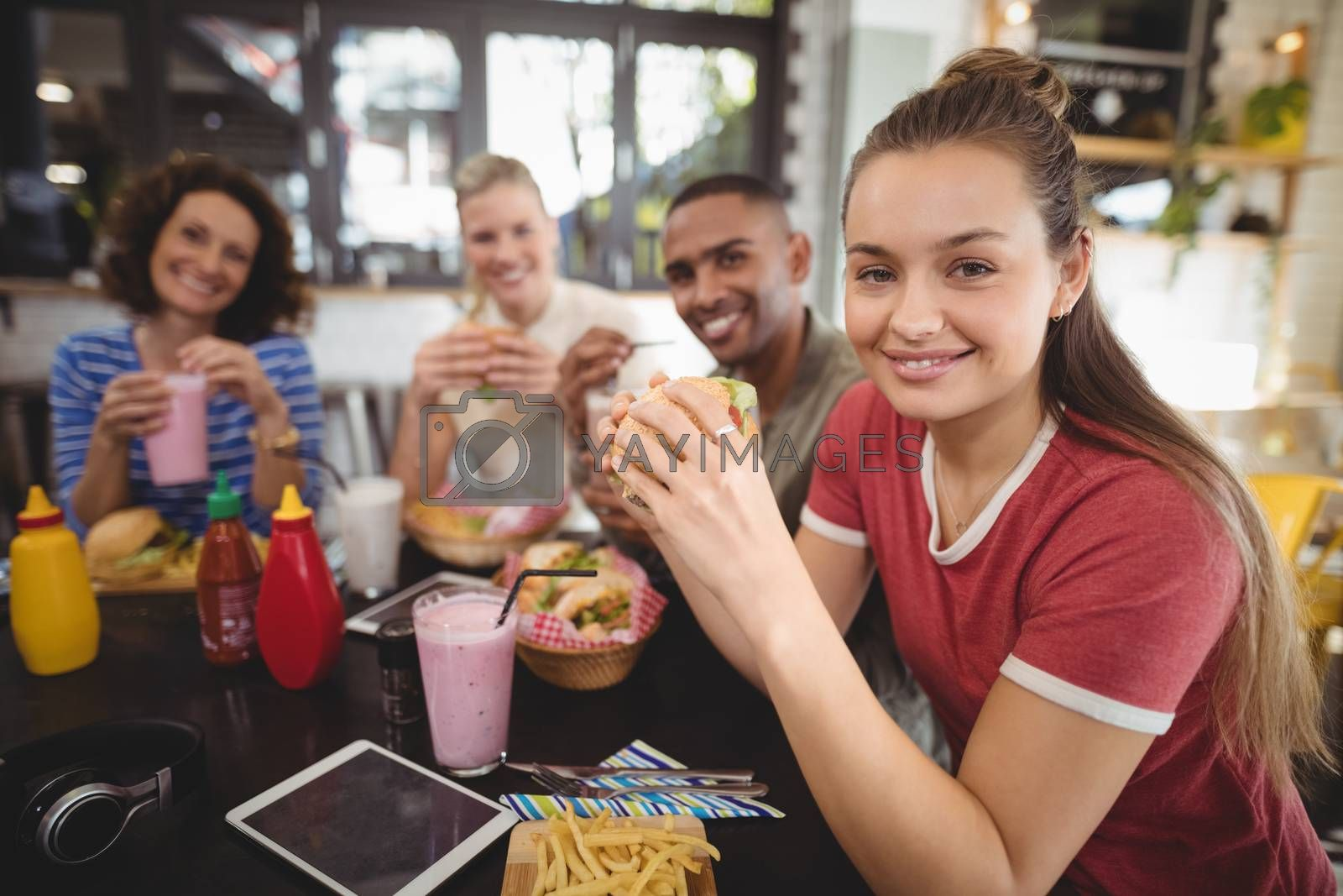 Portrait of smiling young friends sitting with food and drink at coffee shop