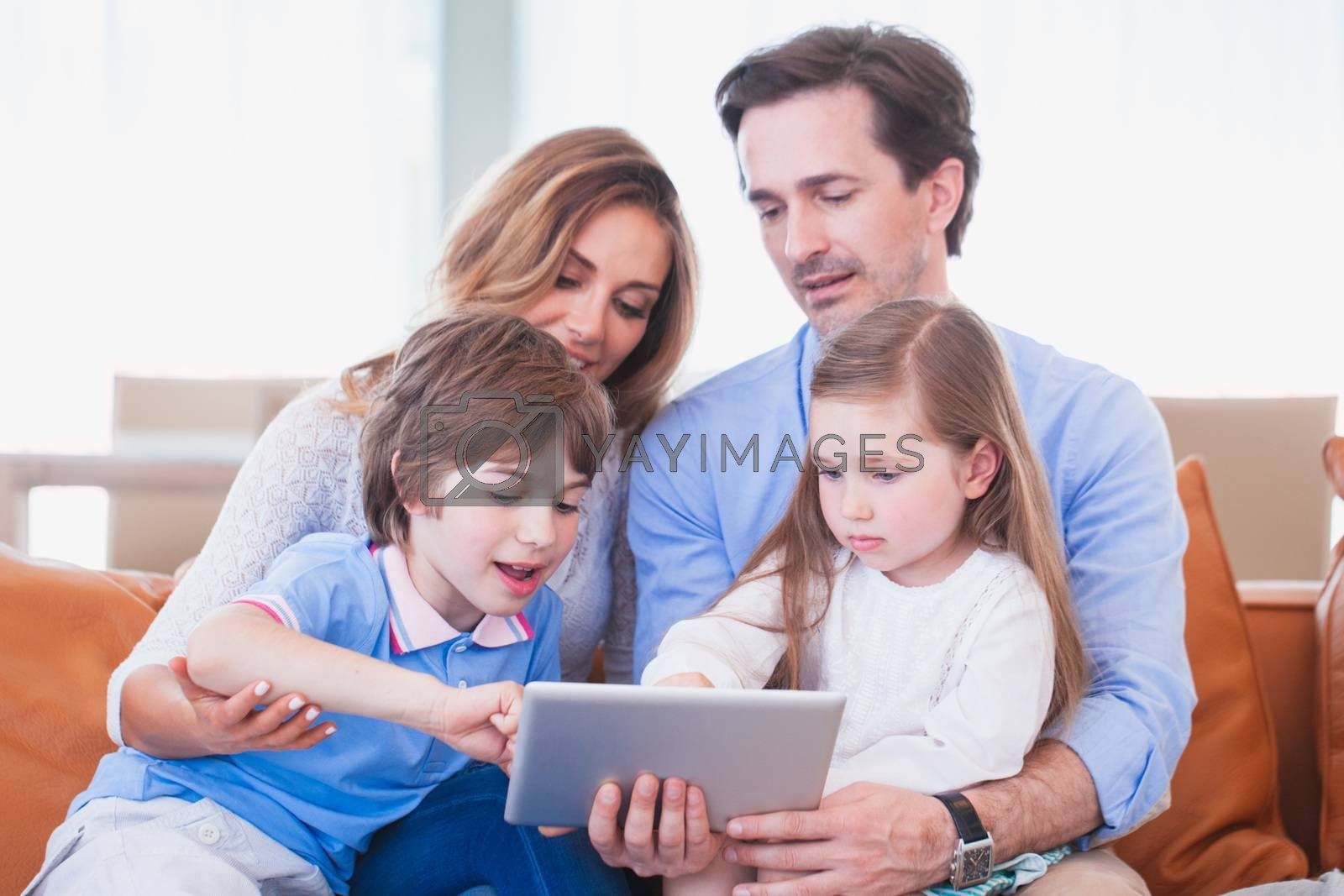 Portrait of happy family with two children sitting on sofa with tablet pc