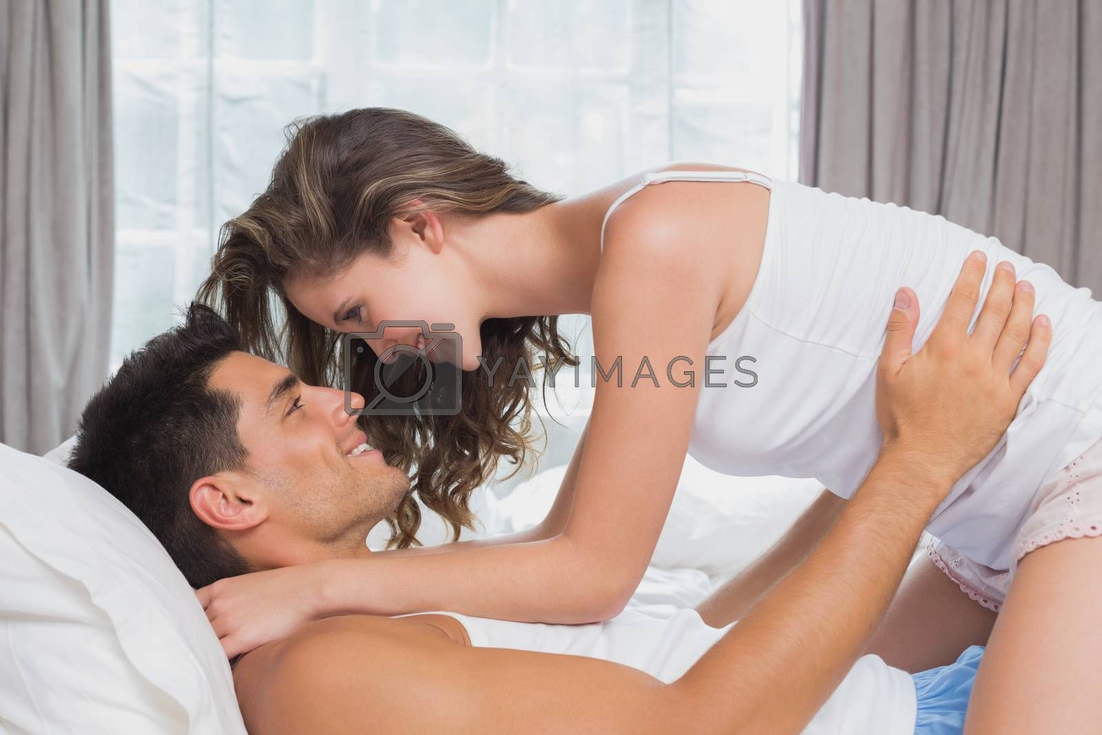 Side view of romantic young couple in bed at home