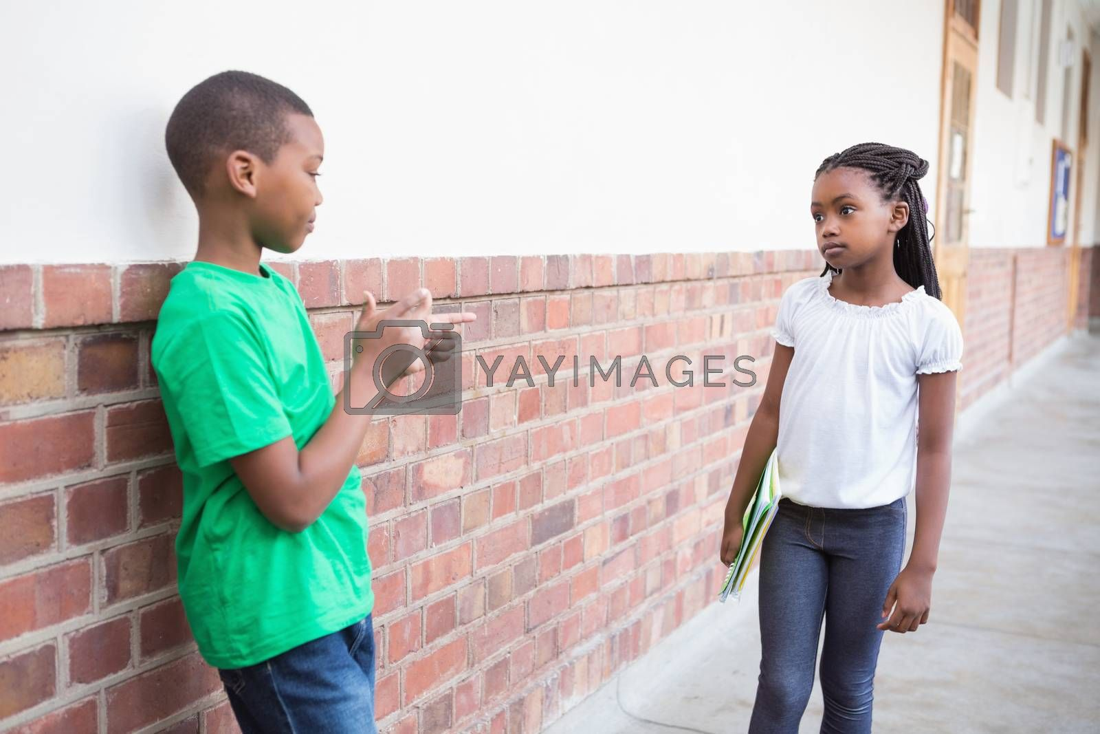 Pupil bullying another in the hall at the elementary school