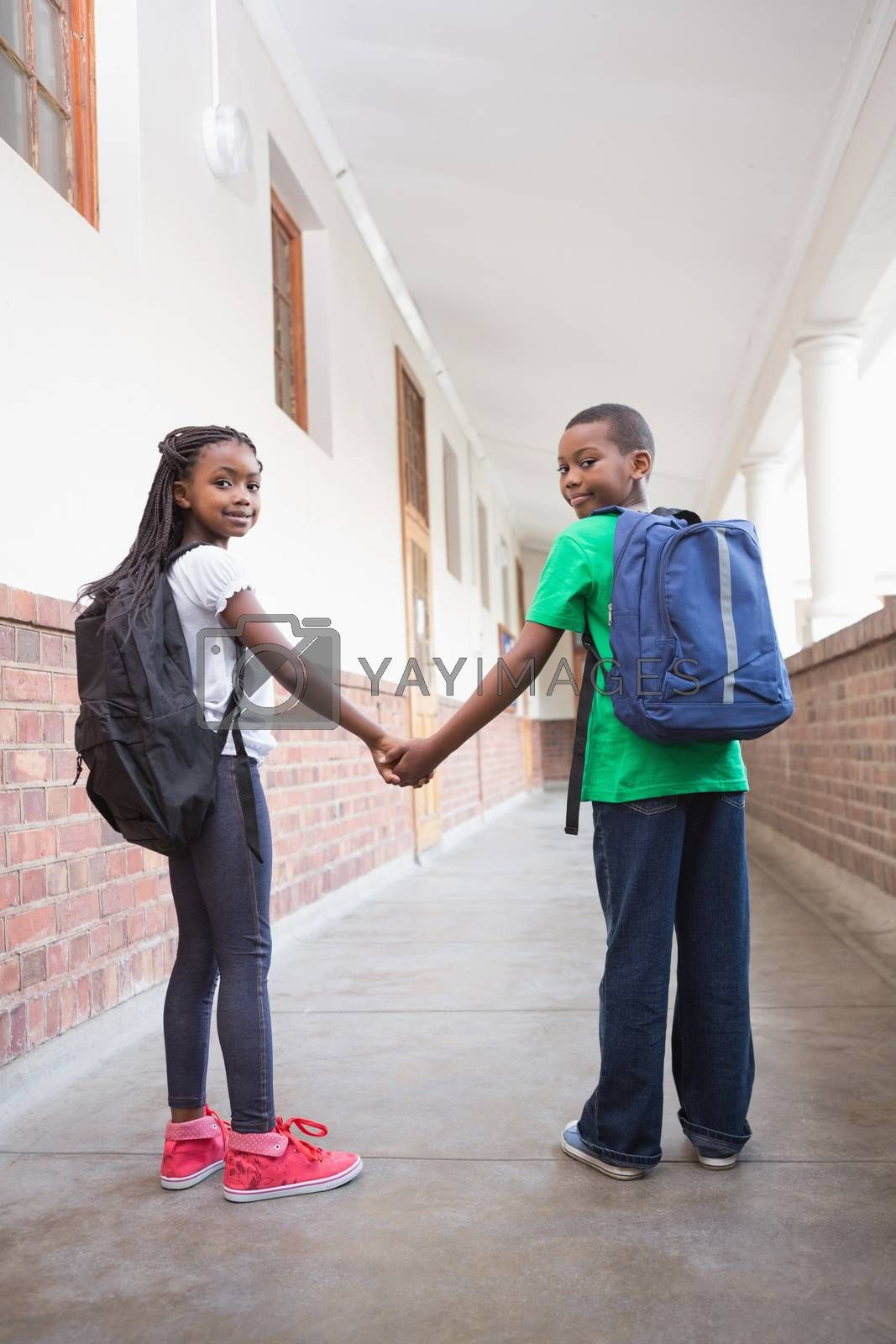 Cute pupils holding hands in corridor at the elementary school