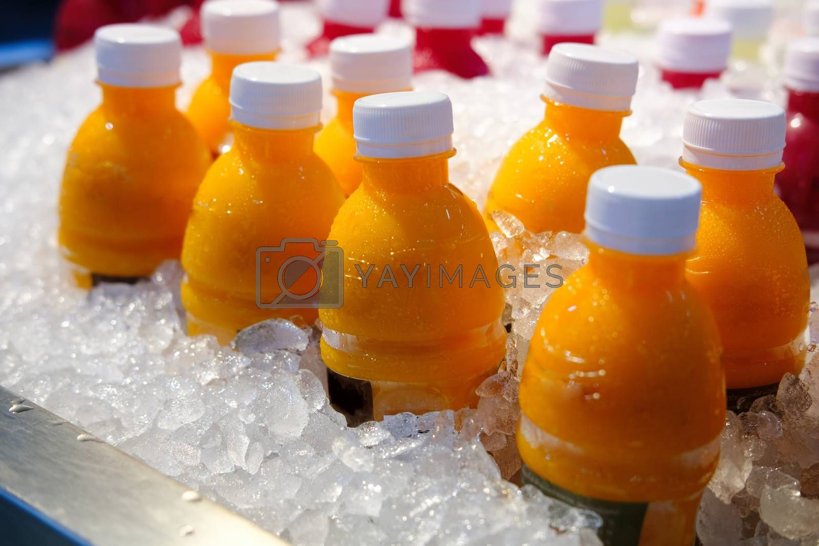 Homemade Fresh Orange juice bottles on the ice box. Mix of plastic bottles on the ice bucket for sale in Thailand food market.