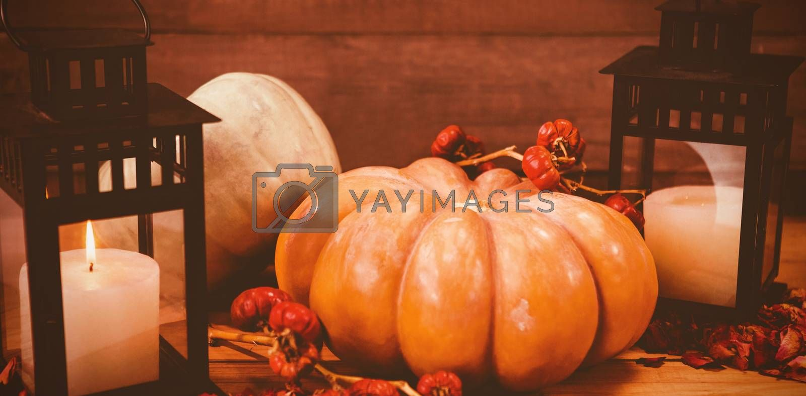 Pumpkins with candles on wooden table during Halloween