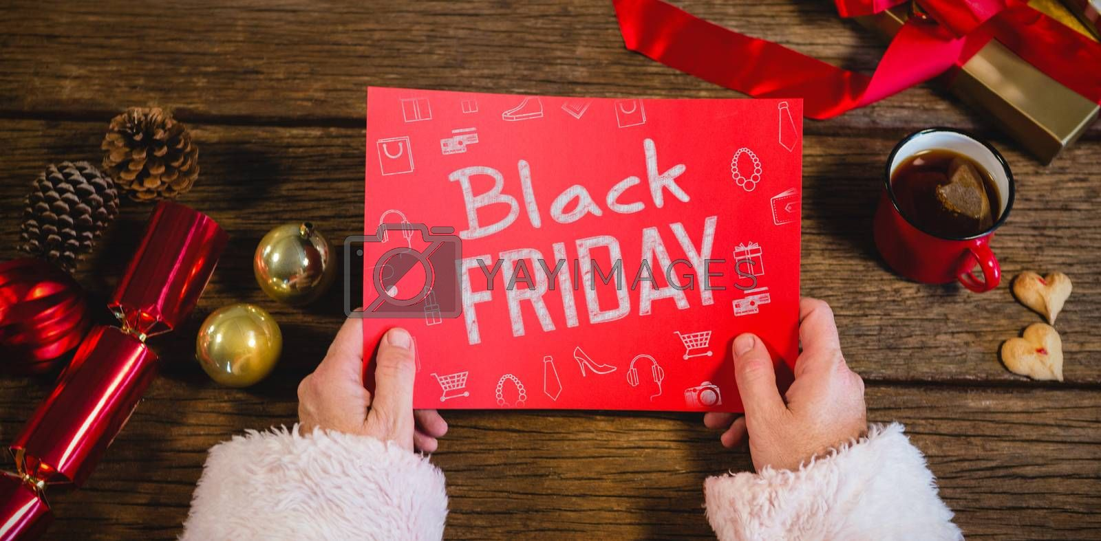 Black friday advert against santa claus holding blank red paper
