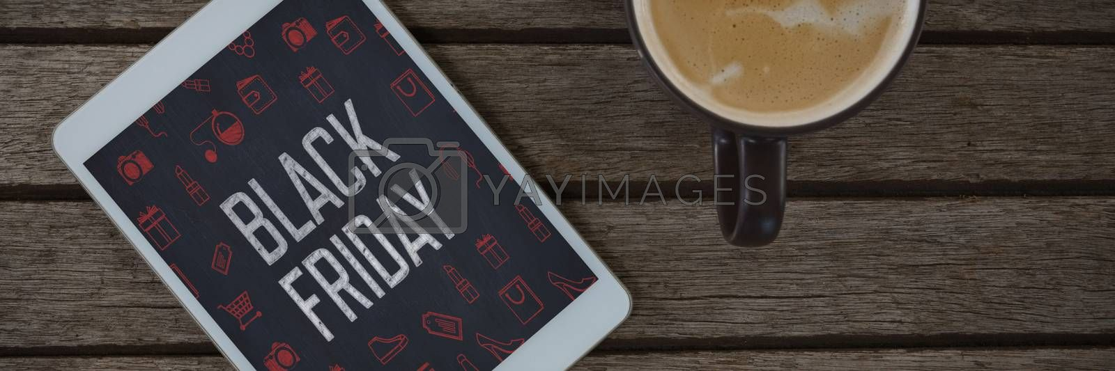 Digital tablet and cup of coffee on wooden plank against black friday advertisement