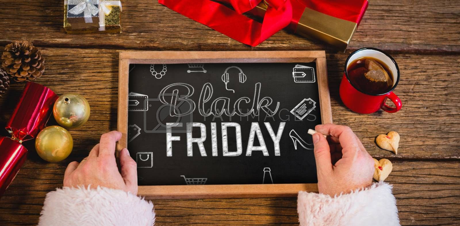 Black friday advert against santa claus holding a slate with merry christmas text