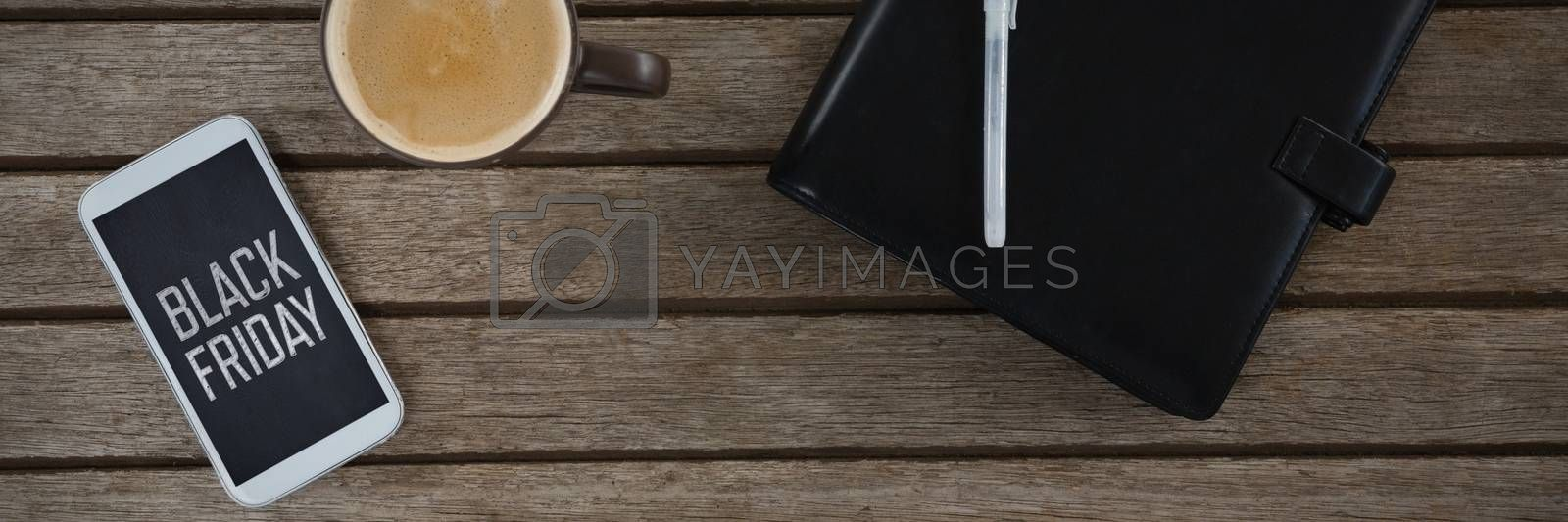 Mobile phone, coffee, pen and organizer on wooden plank against black friday advert