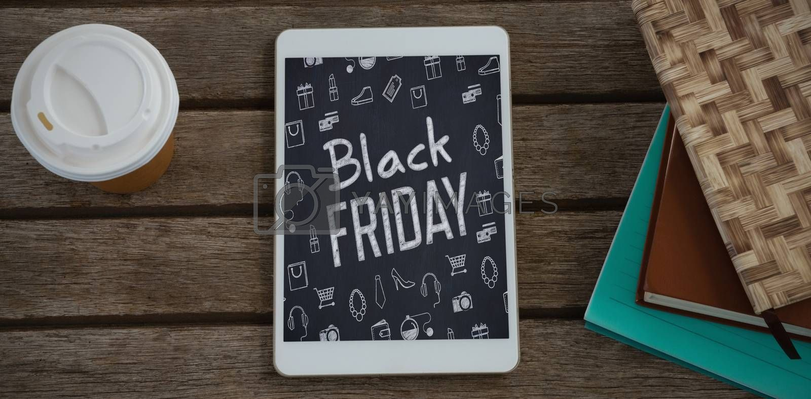 Disposable glass, books and digital tablet on wooden plank against black friday advert