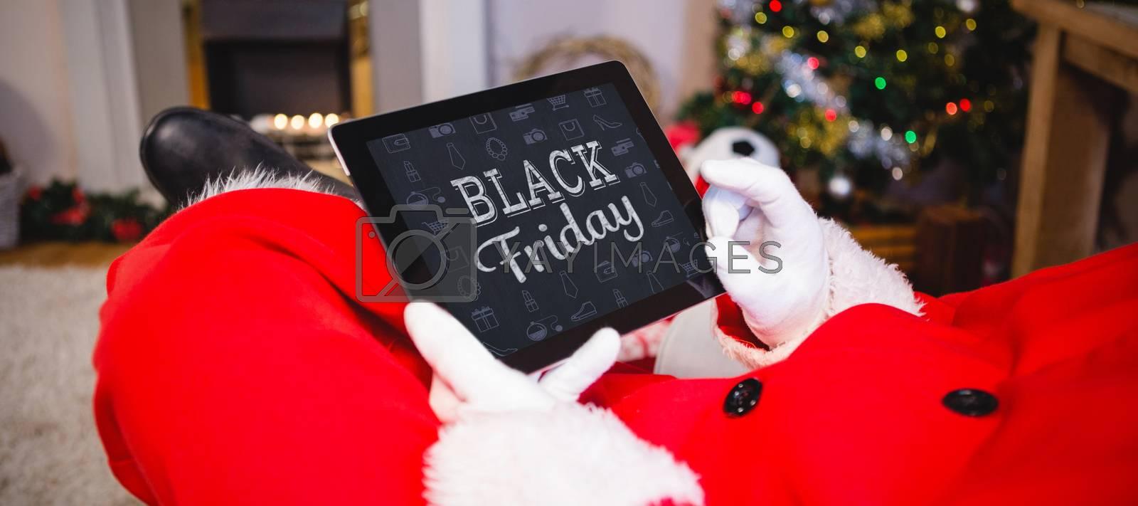 black friday against santa claus sitting and using digital tablet