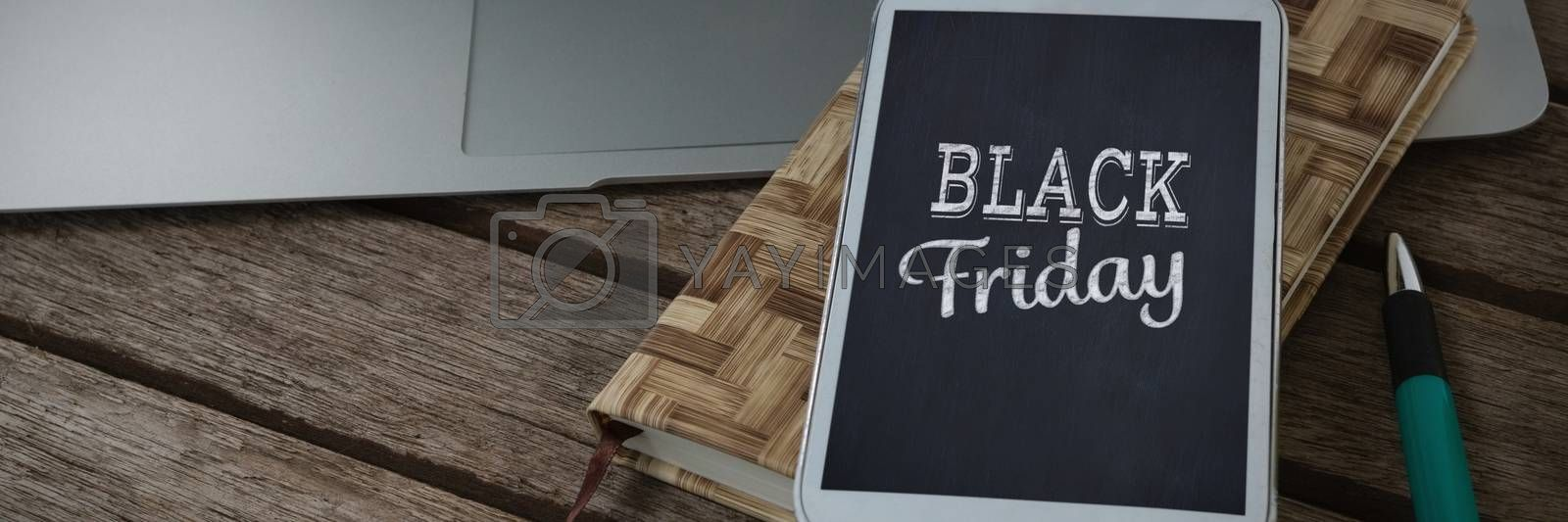 Laptop, mobile phone, dairy and pen on wooden plank against black friday