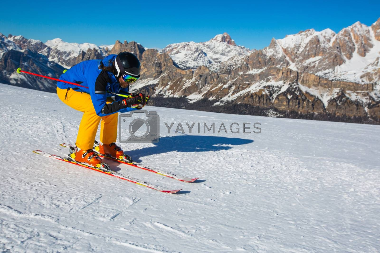 Male skier in blue and yellow clothes on slope with mountains in the background at Cortina d'Ampezzo Faloria skiing resort area Dolomiti Italy