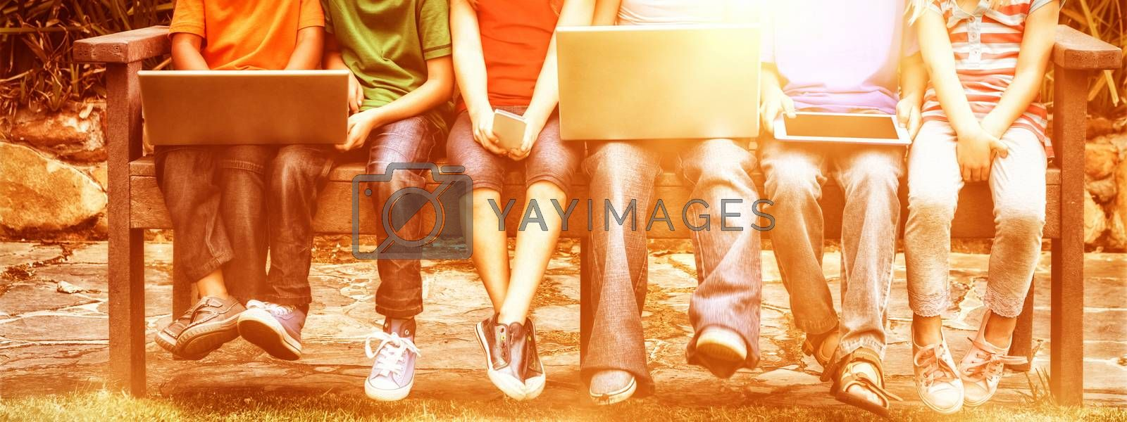 Portrait of smiling children with technologies sitting on bench