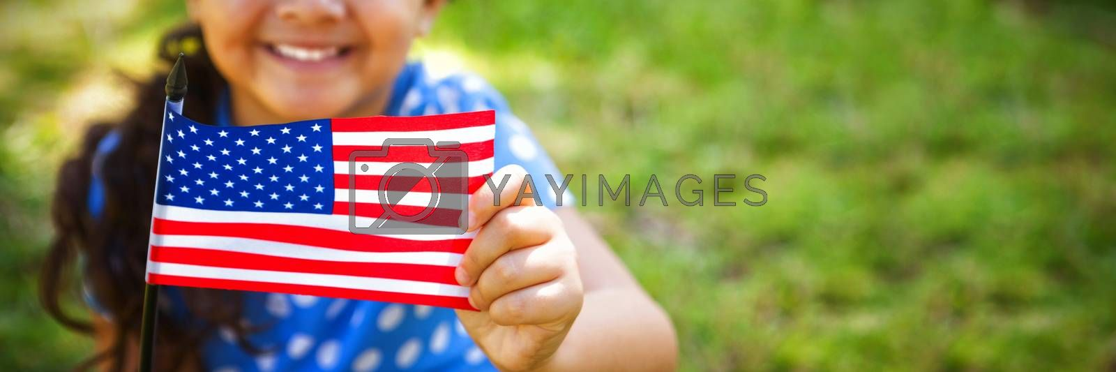Portrait of girl holding American flag while standing at park