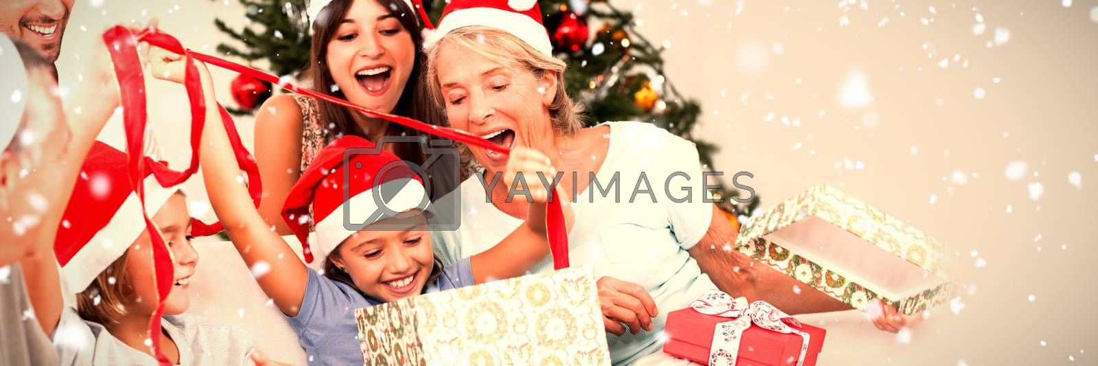 Happy family at christmas opening gifts together against snow falling