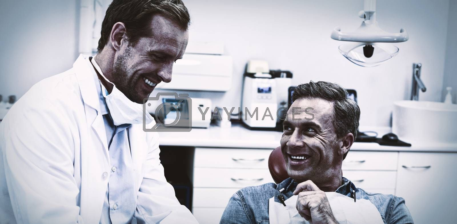 Dentist discussing over digital tablet with male patient in dental clinic