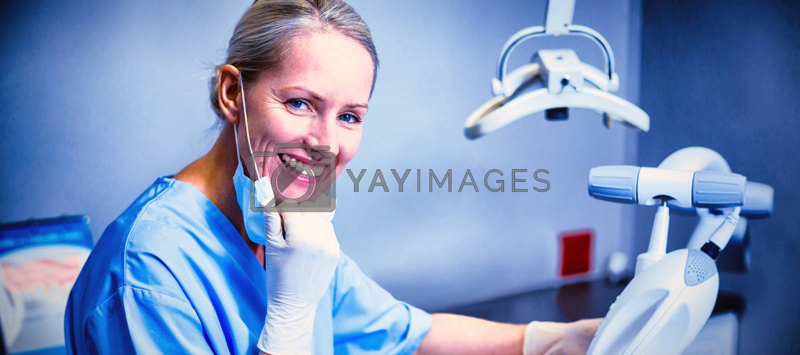 Portrait of dental assistant examining young patient mouth in clinic