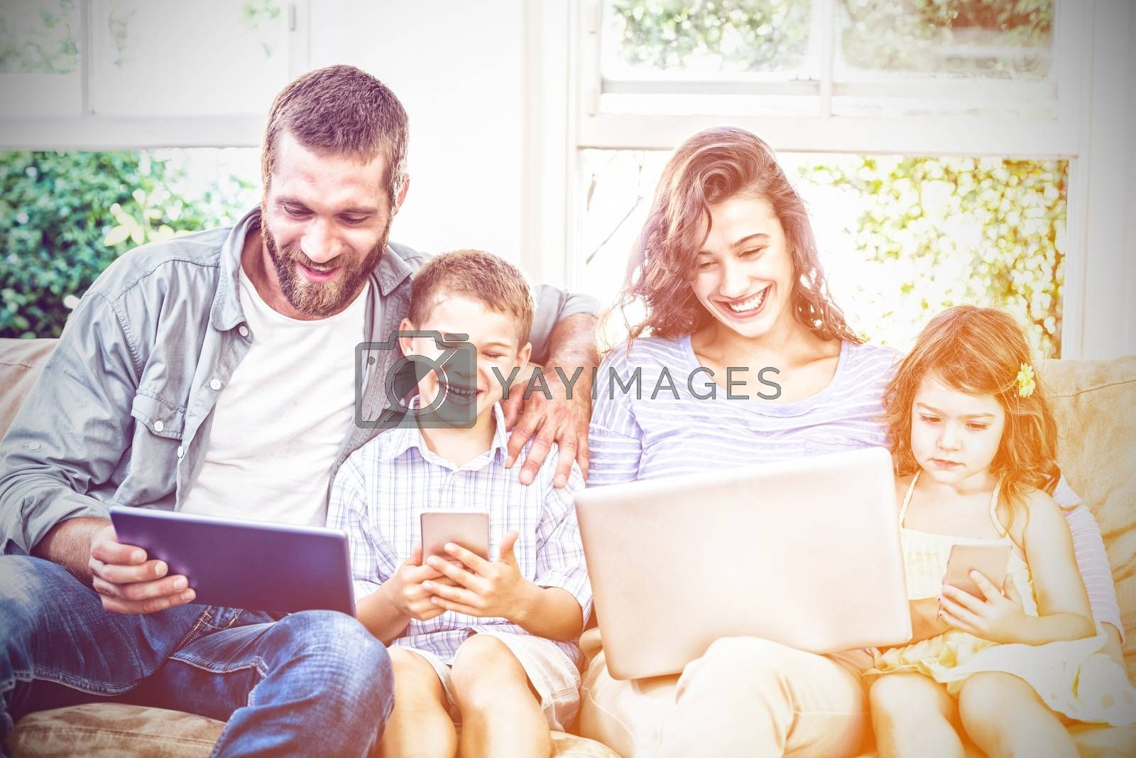 Family using technologies while sitting on sofa at home