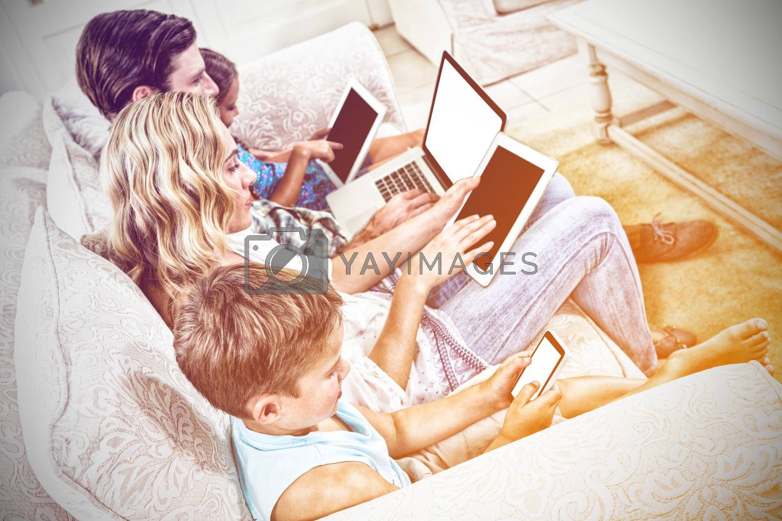 High angle view of family using various technologies while sitting on sofa at home