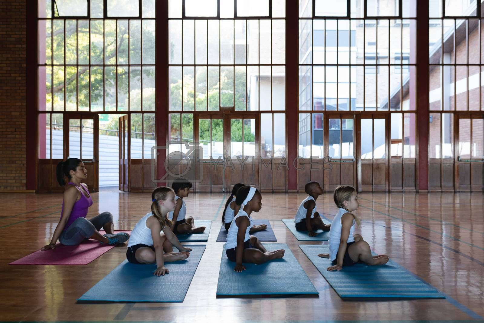 Side view of female yoga teacher and schoolkids doing yoga and meditating on a yoga mat in school