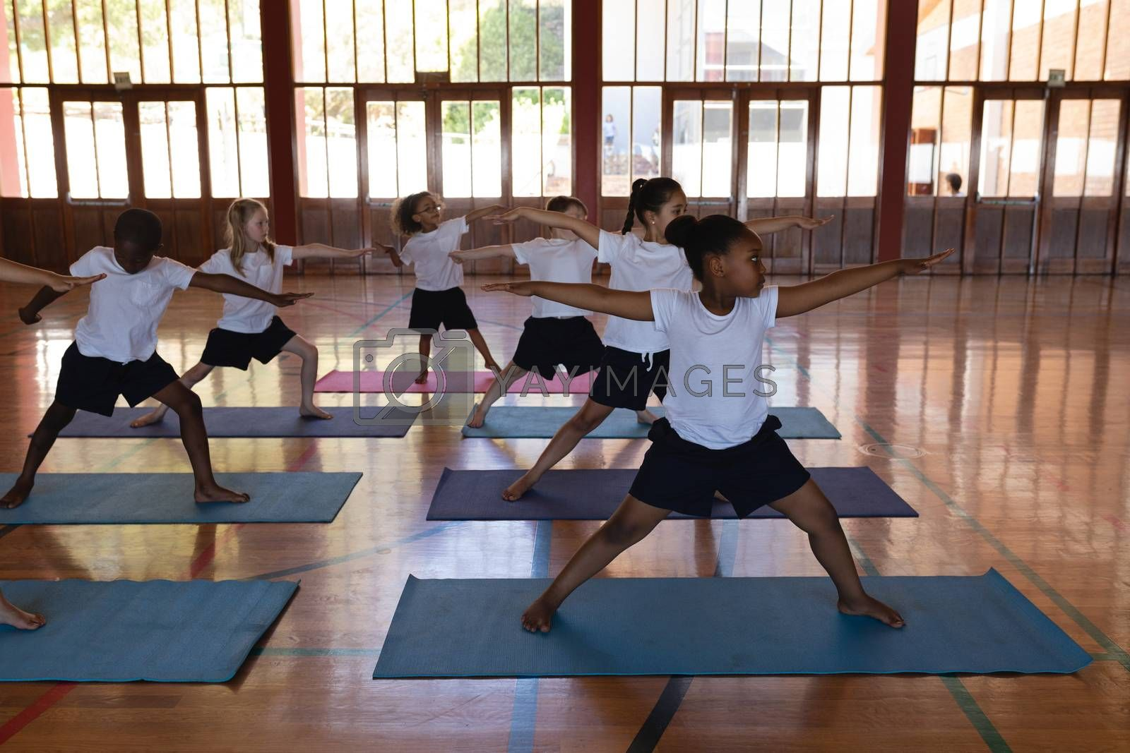 Front view of schoolkids doing yoga on a yoga mat in school gymnast