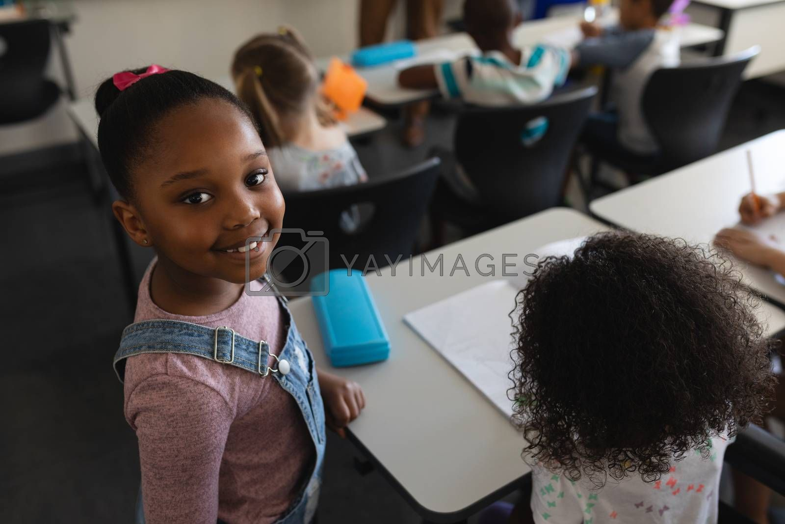 Smiling black schoolgirl standing and looking at camera in classroom of elementary school