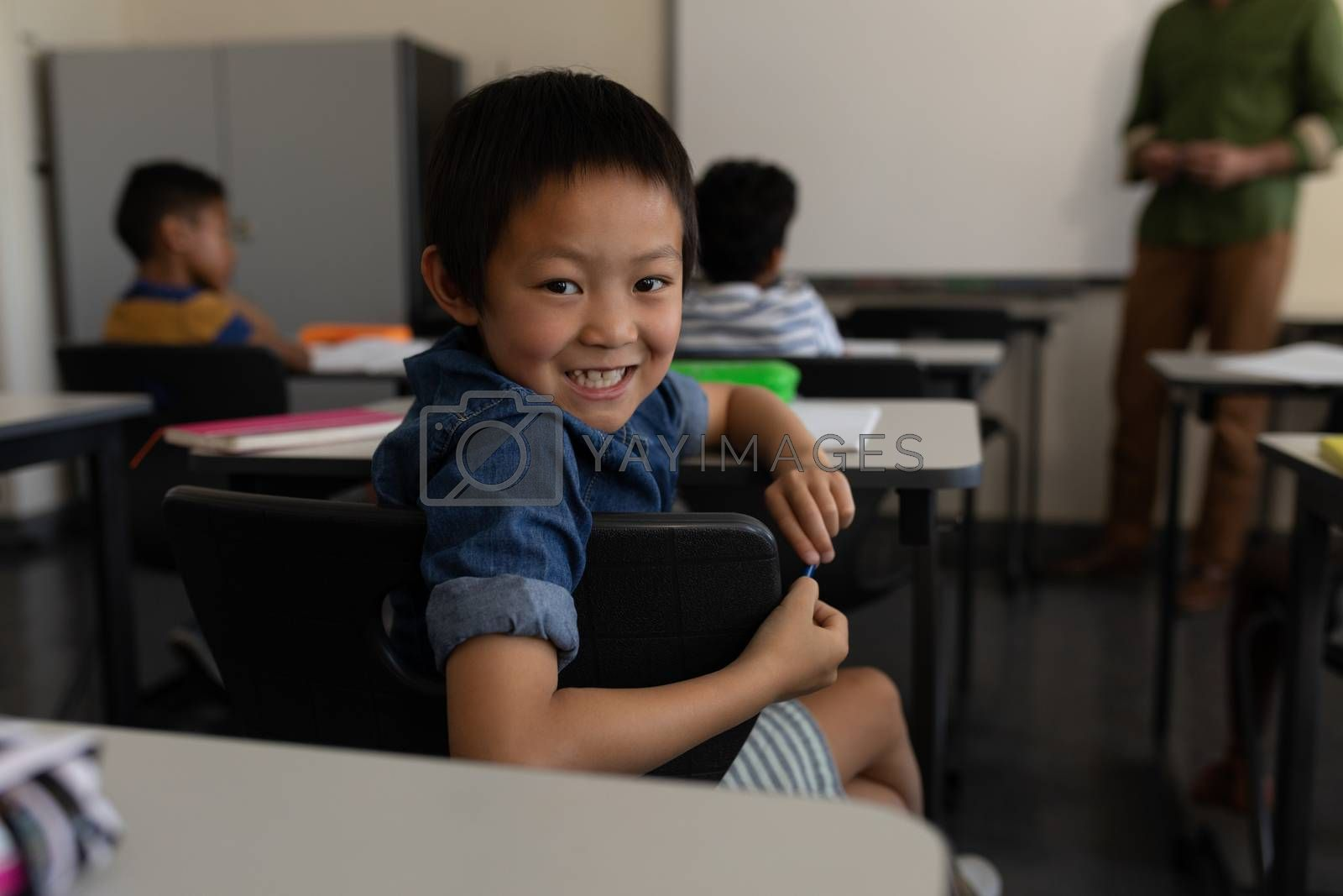 Happy schoolboy smiling and looking back in classroom of elementary school