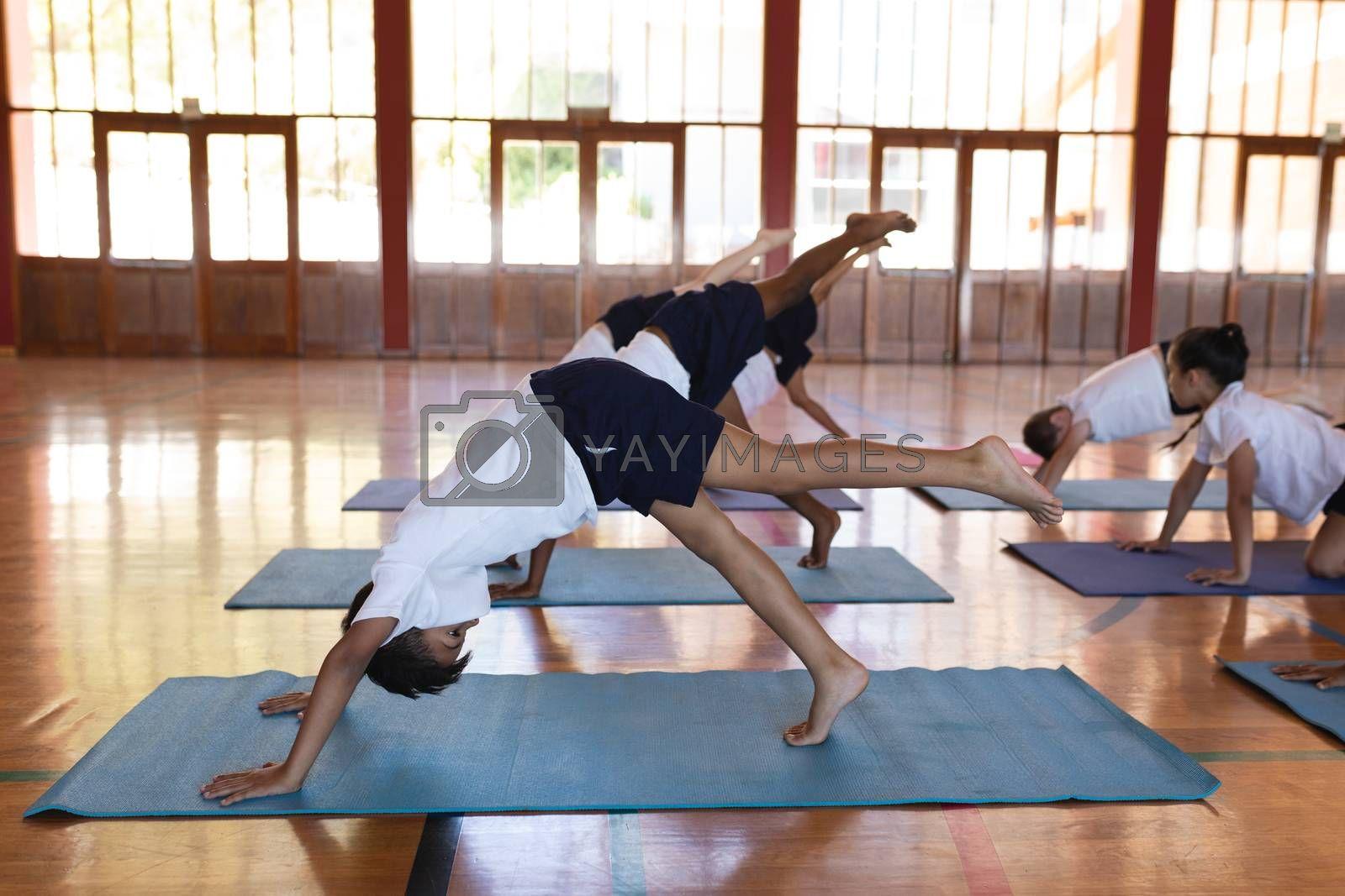 Side view of schoolkids doing yoga position on a yoga mat in school gymnast