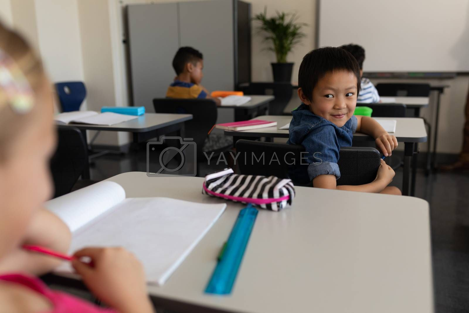 Happy schoolboy looking back in classroom of elementary school