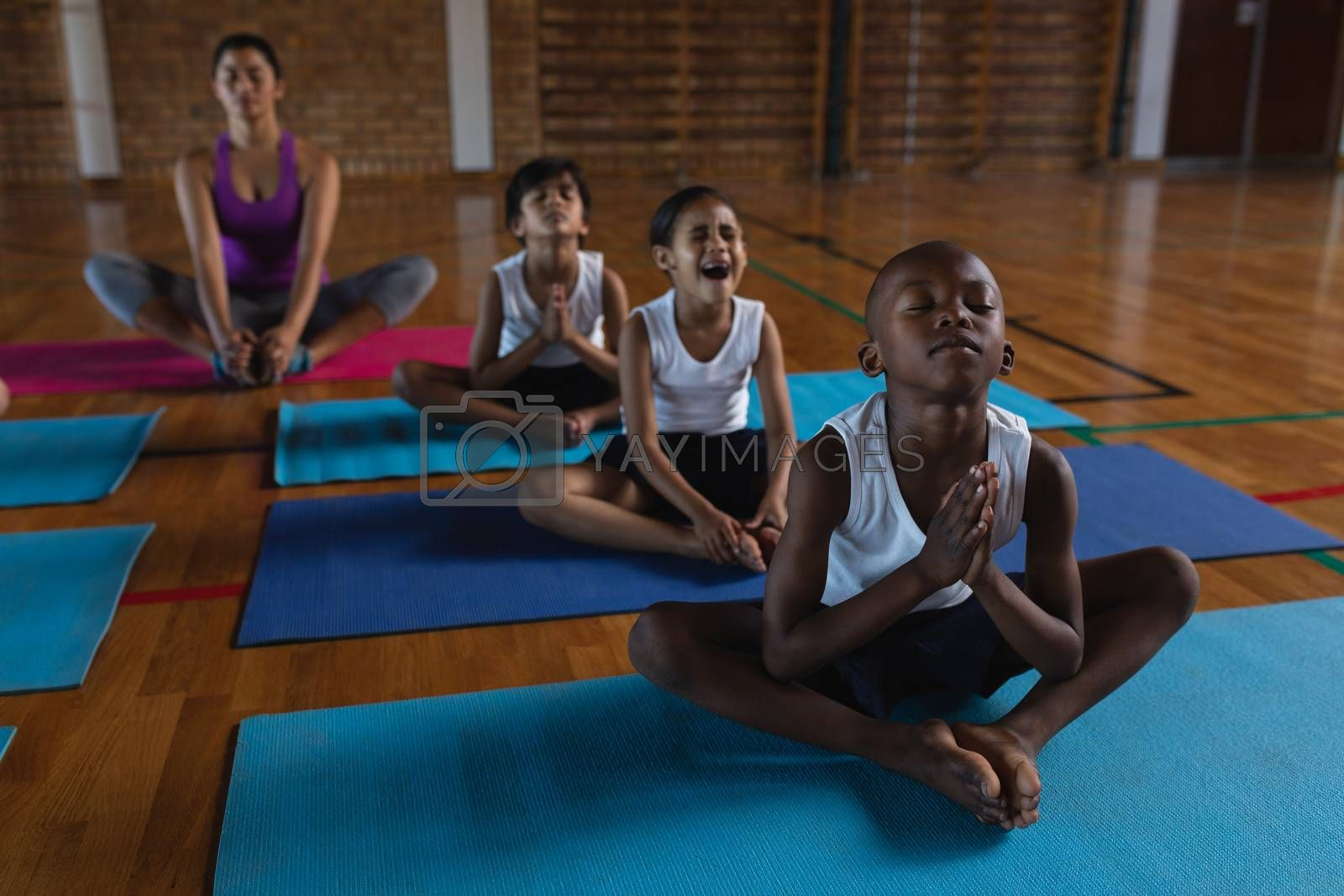 Front view of female yoga teacher and schoolkids doing yoga and meditating on a yoga mat in school