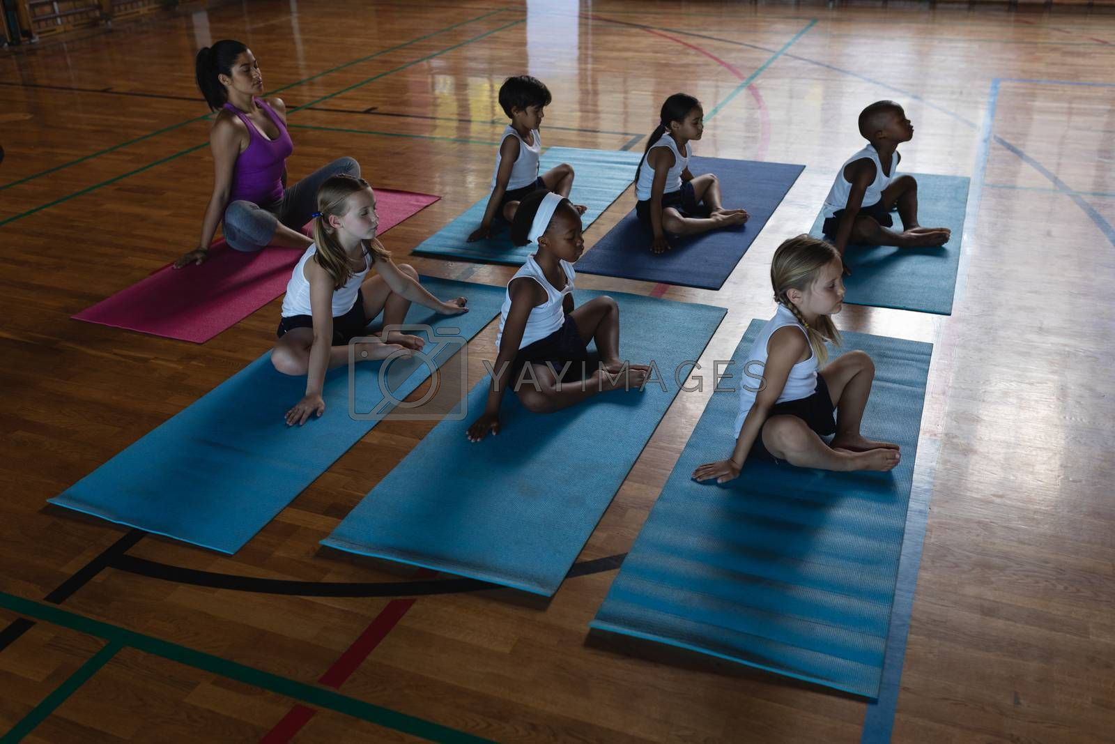High angle view of female yoga teacher and schoolkids doing yoga and meditating on a yoga mat in school