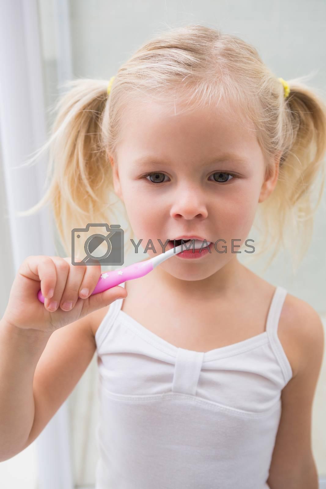 Cute girl brushing her teeth at home in the bathroom