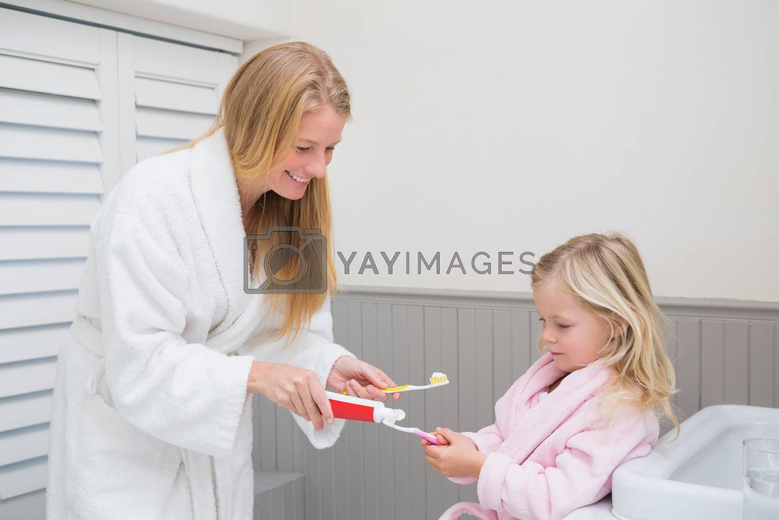 Happy mother and daughter brushing their teeth at home in the bathroom