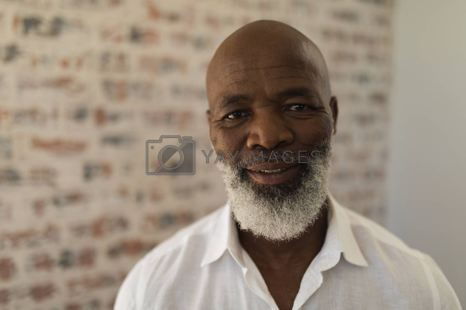 Portrait of black senior man smiling and standing at home