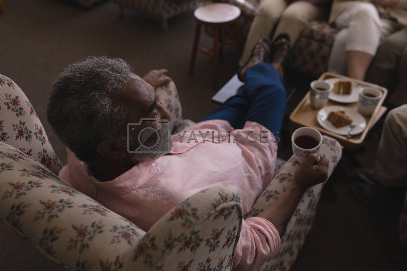 Senior man having black coffee in living room by Wavebreakmedia