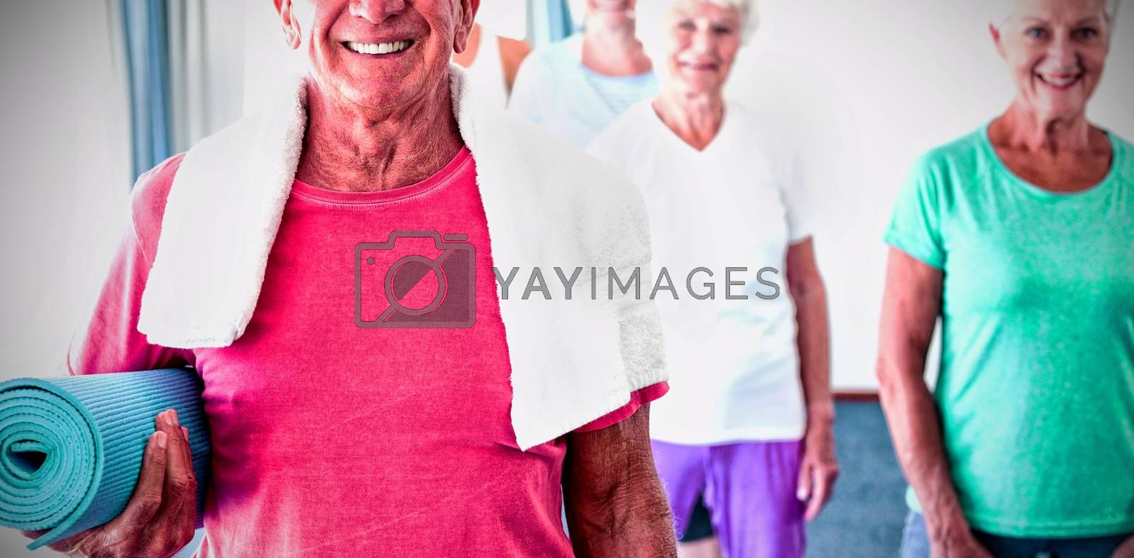 Senior man holding yoga mat during yoga class