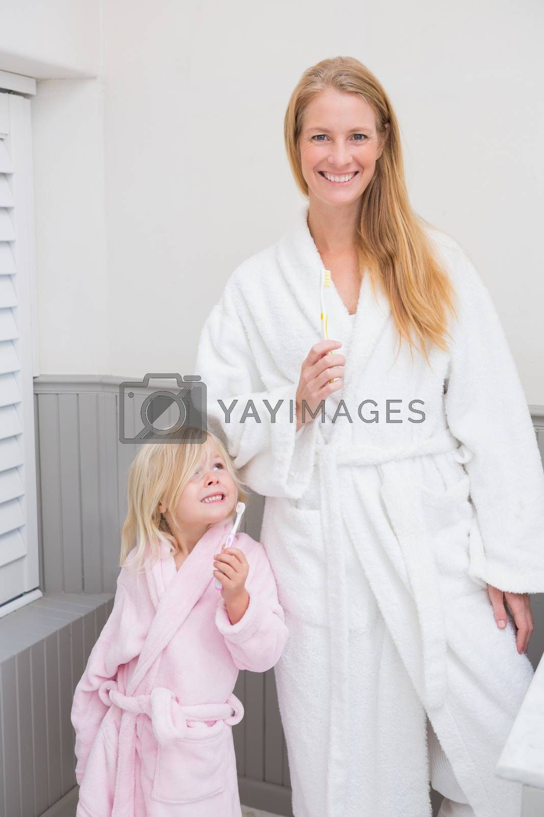 Mother and daughter brushing their teeth at home in the bathroom