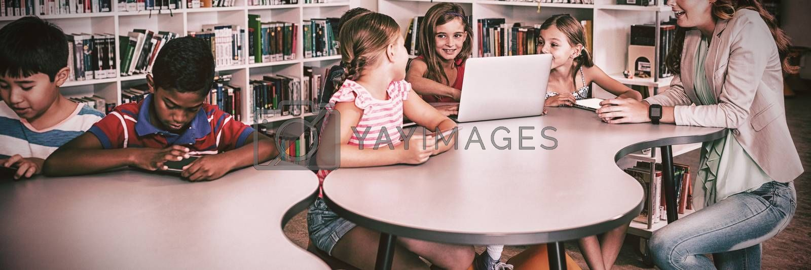 Teacher using technology with pupils in library